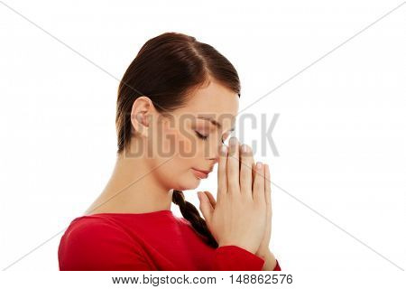 Young woman praying with her hands together