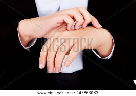 Young elegant woman scratching her hand