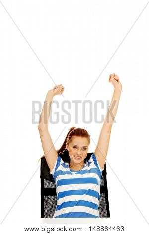 Teenage woman sitting behind the desk with arms up