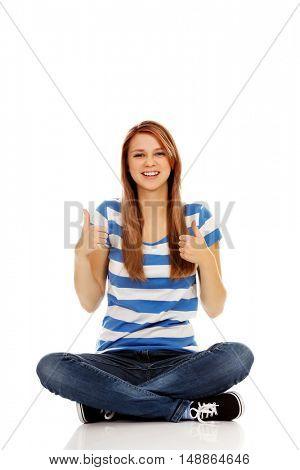 Happy teenage woman sitting with cross legged