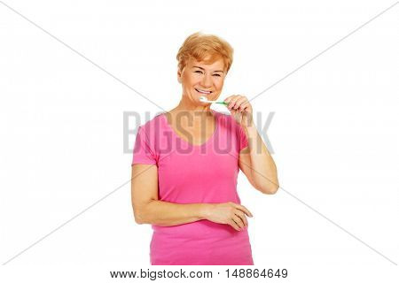 Smiling senior woman brushing teeth
