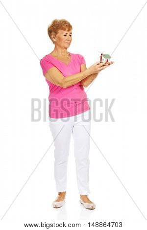 Senior woman holding house model