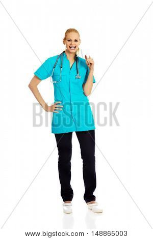 Happy dentist woman with stethoscope holding tooth model