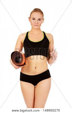 Woman ready for workout with yoga mats showing thumb up
