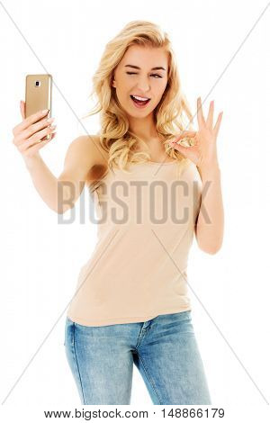 Happy young woman showing perfect sing and taking pictures of herself at smart phone