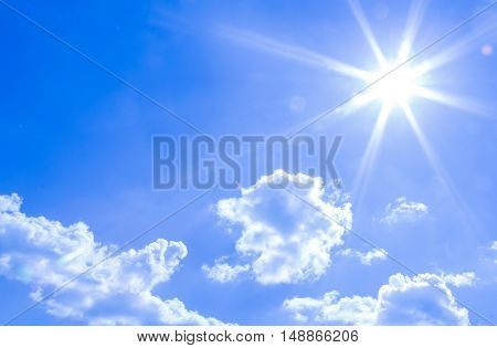 natural lens flare and radiating rays in a blue sky with clouds. You can apply for sky background, sky backdrop, sky wallpaper, sky with text and everything about sky background concept.