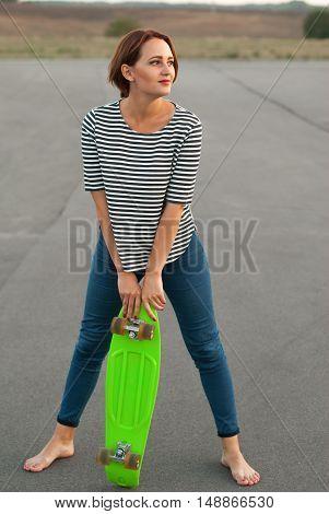 Girl with skateboard standing barefoot on the asphalt.