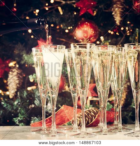 Filling Up Glasses For Party. Glasses Of Champagne With Christmas Tree Background. Holiday Season Ba