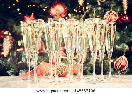 Glasses Of Champagne With Christmas Tree Background. Many Glasses For Party. Holiday Season Backgrou