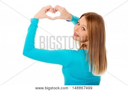 Smiling teenage woman making heart shape