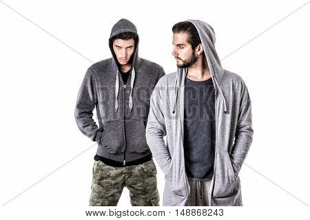 Two young men wearing military and sport clothes. Wearing hoods on heads. Studio shot.