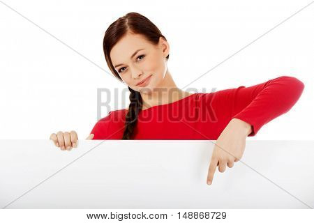 Beautiful student woman pointing on blank board