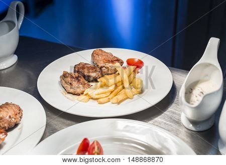 Lamp chop with french fries and tomatoes. white plates