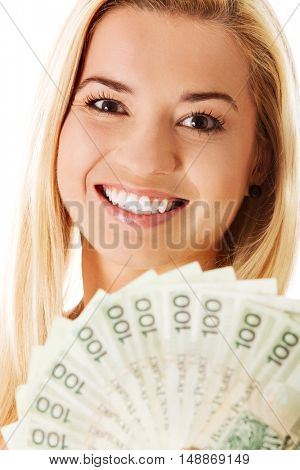 Attractive young lady holding cash and happy smiling over white background.