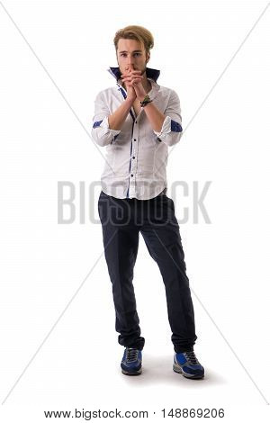 Needy, desperate young man pleading with hands joined as if praying to camera, isolated
