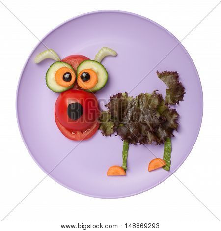 Funny dog made of tomato salad and cucumber on plate