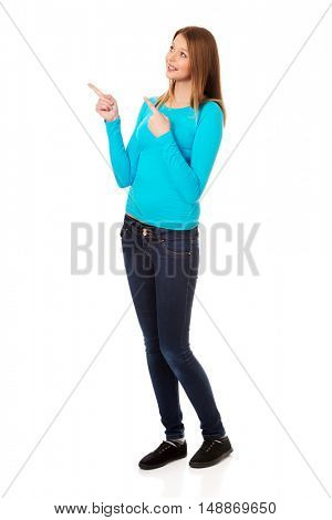 Young woman pointing with both hands