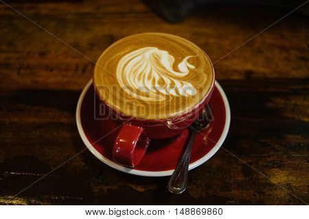 Close up overhead view of a cup of strong frothy coffee on a rough textured wooden surface with dark vignetting and a highlight around the mug with copyspace