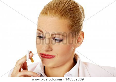 Business woman holding broken cigarette