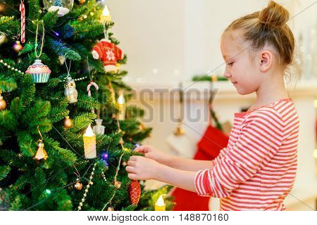 Adorable little girl decorating Christmas tree with colorful glass baubles at home