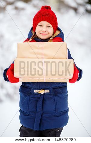 Adorable little girl wearing warm clothes outdoors on Christmas day holding gifts
