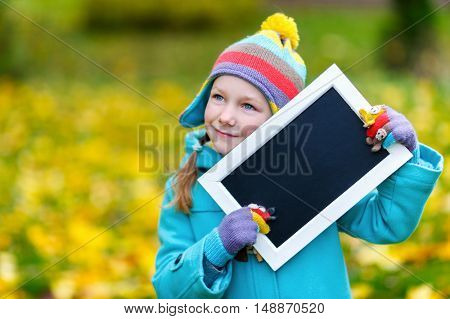 Adorable little girl holding empty blackboard at beautiful autumn park