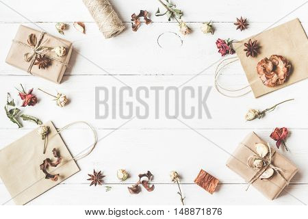 Autumn composition. Frame with gift paper bags autumn leaves anise stars dried flowers. Workspace. Top view flat lay