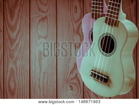 Part of an acoustic guitar on a gray wooden background