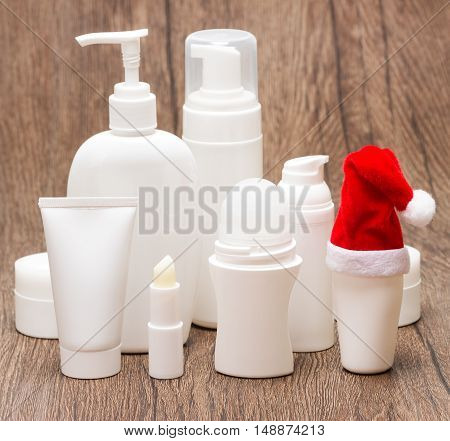 Christmas skincare cosmetics. Various cosmetic products for face and body care with Santa hat on wooden surface. Christmas sale or gift concept, focus on hat