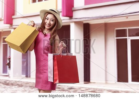 Pretty Asian Girl With Hat Standing In Front Of A Shop