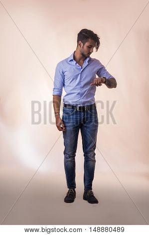 Portrait of brunette young man in light blue shirt and jeans, checking the time on wrist watch while standing in studio shot, isolated against white background. Full length photo