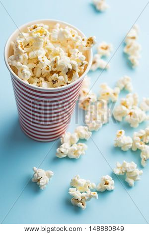 Popcorn in paper cup on colorful background.