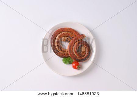 grilled spiral pork sausages on white plate