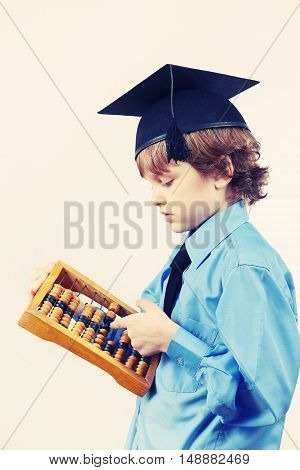 Little boy in academic hat with old abacus on a light background gently toned