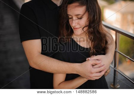 Young loving couple outdoors hugging and looking away, future and relationships concept