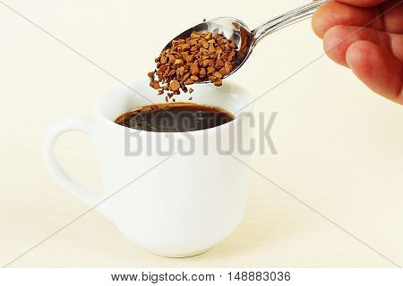 Hand pours granulated coffee from a spoon in a coffee cup gently toned
