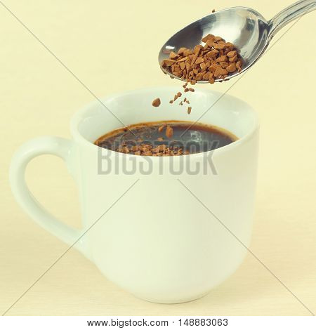 Granulated coffee is poured from a spoon in a cup gently toned