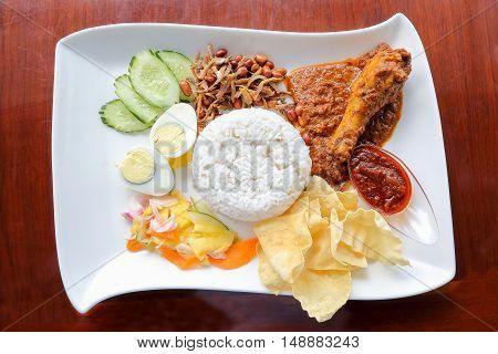 Nasi Lemak with chicken rendang egg fried anchovies peanuts fish chips salad and sambal