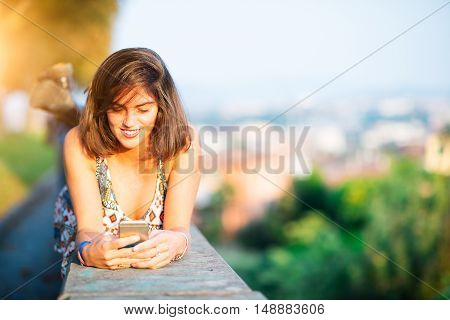 Young Beautiful Girl On A Wall In A City Sends Message With Social Network From His Smart Phone
