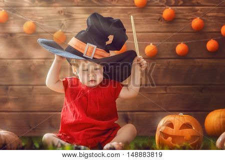 Happy Halloween! Cute cheerful little witch with a magic wand. Beautiful child baby girl in witch costume sitting on grass.