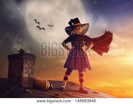 Happy Halloween! Cute little witch on the roof. Beautiful young child girl in witch costume outdoors.