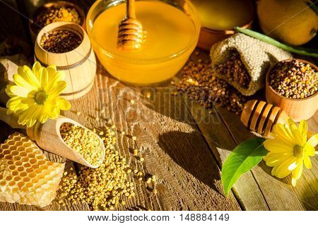 Honeycombs ,honey, Pollen,and Flowers On A Wooden Table
