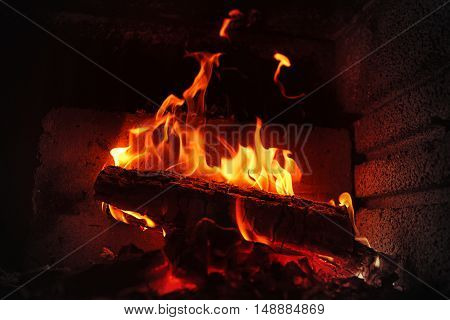 Burning fireplace. Burning wood in brick fireplace. Fireplace with a blazing fire. Fire in a fireplace. Hot fire in darkness on fireplace. Burning and glowing pieces of wood in Fireplace.