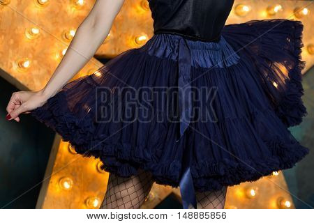 Woman wearing blue lace tutu skirt and mesh stockings posing over dark background with glowing star close up. Actress or dancer playing on stage.
