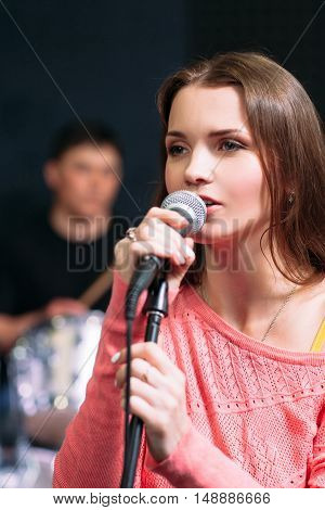 Young attractive woman singing karaoke in bar. Beautiful girl enjoying her evening pastime with microphone, close-up portrait