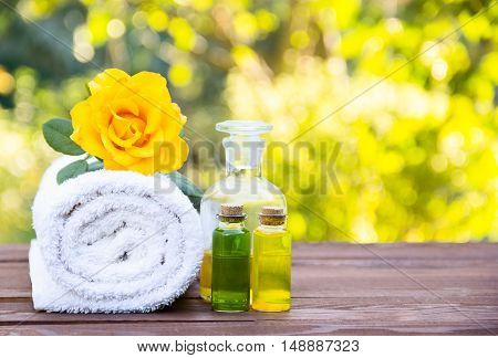 Massage oil, white towel and flower elixirs. Cosmetics for saunas and spa treatments. Spa concept. Essential oils. Cosmetics for saunas and spa treatments. Fragrant yellow rose. Copy space.