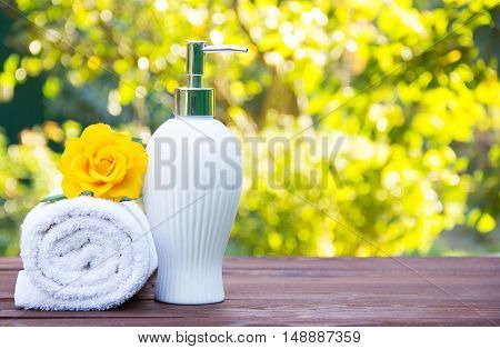 Soap dispenser, towel and fragrant yellow rose. Spa concept. Health and beauty. Body Lotion with rose oil. Natural green background. Green blur. Copy space.