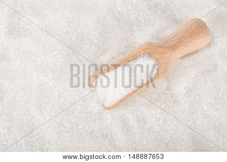 Heap of white sugar with a wooden spoon top view. White sugar. Wooden scoop on white sugar background top view