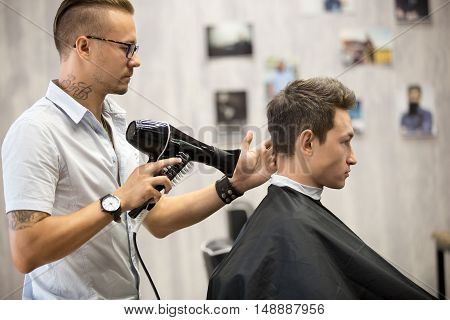 Hairdresser Styling Hair For Male Client