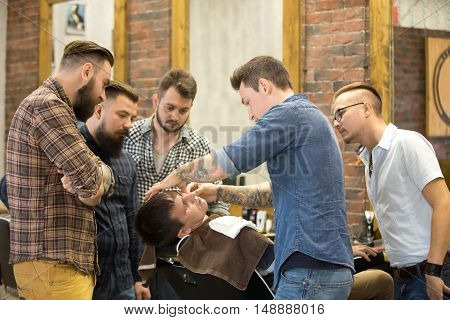 Teacher training group of students in beard shaving with metal straight razor in hairsalon. Interior shot of learning process in modern barbershop